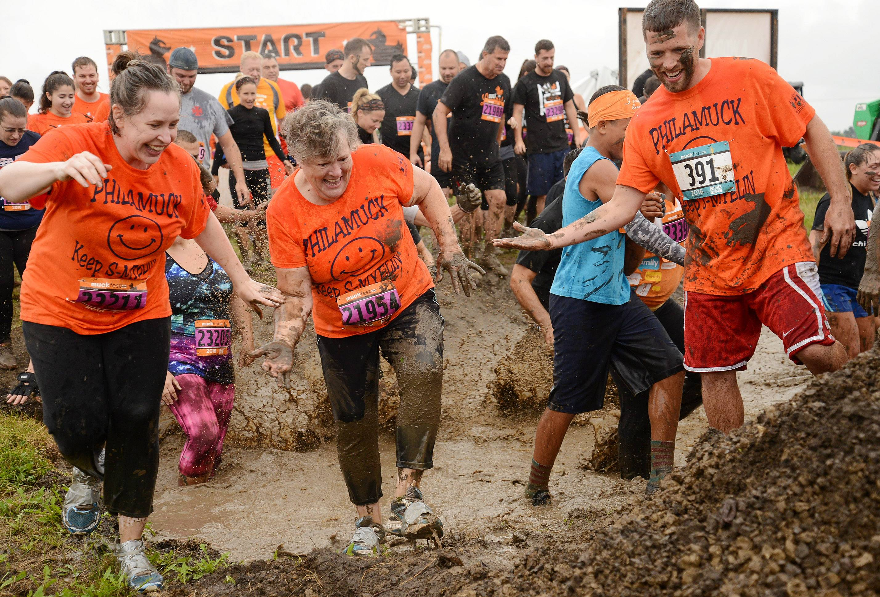 Rosemary Karner of McHenry, center, gets help navigating the mud course during Muckfest MS at the Lake County Fairgrounds.