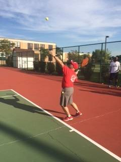 Athletic director Dan Jones participates in a Hinsdale Central tennis practice.
