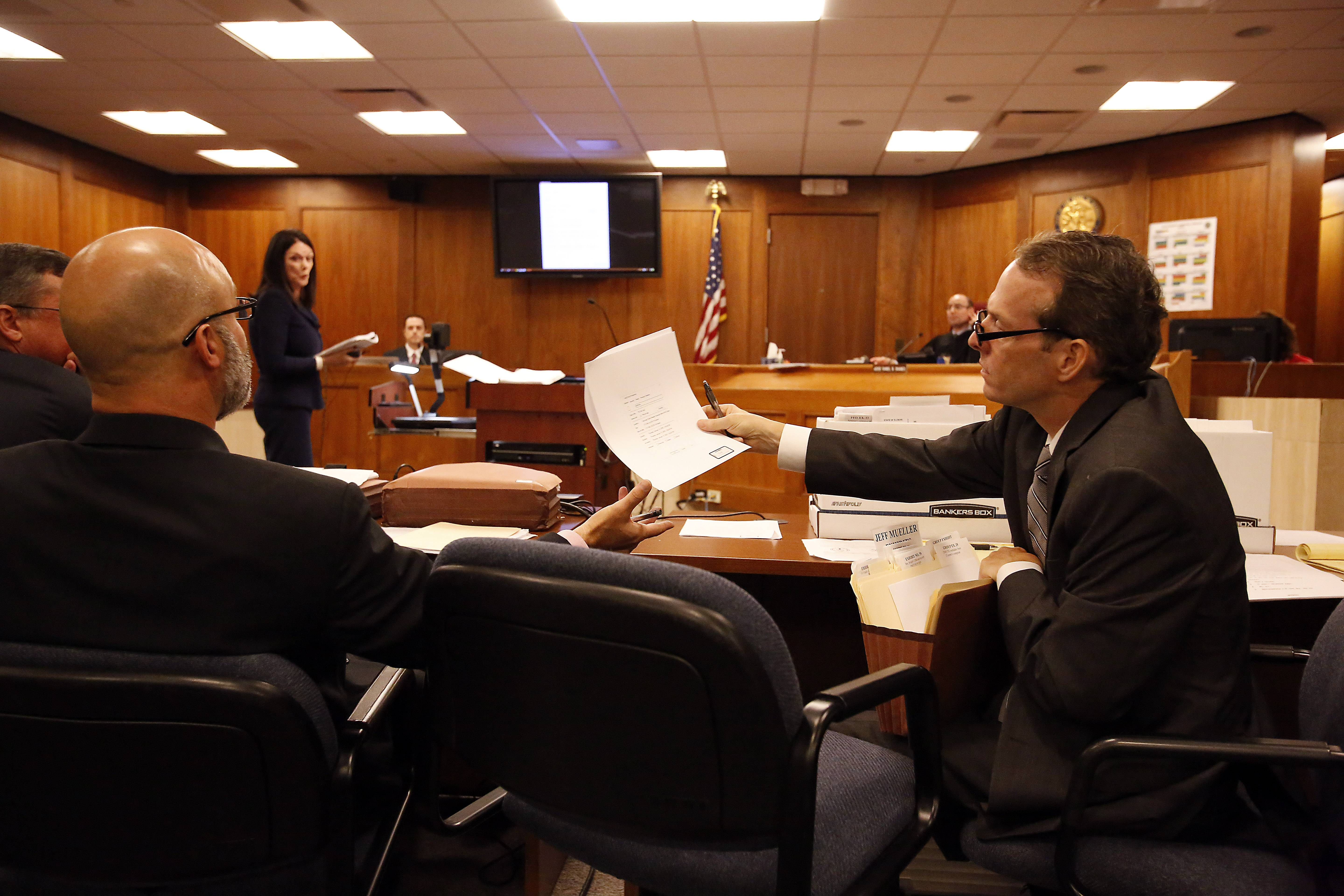 Defense attorney Douglas Johnson hands Lake County Assistant State's Attorney Steve Scheller papers during Friday's hearing to determine if Melissa Calusinski, 29, of Carpentersville, deserves a new trial in the death of a toddler at a Lincolnshire day care center.