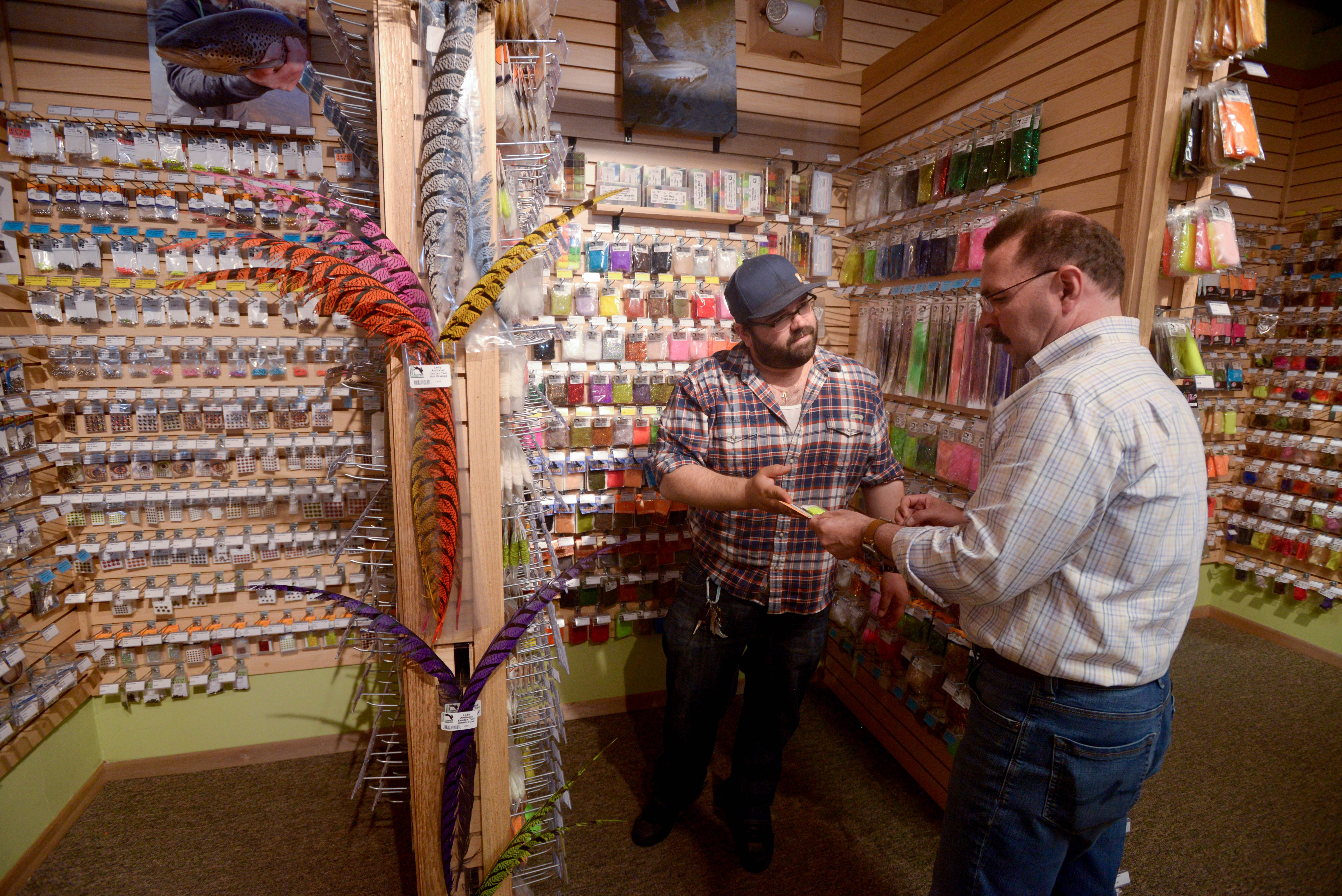 Jeremy Spaccapaniccia of DuPage Fly Fishing Co. in Naperville talks with former fly tying student Chris Camp of Naperville as he searches for the right material for his flies.