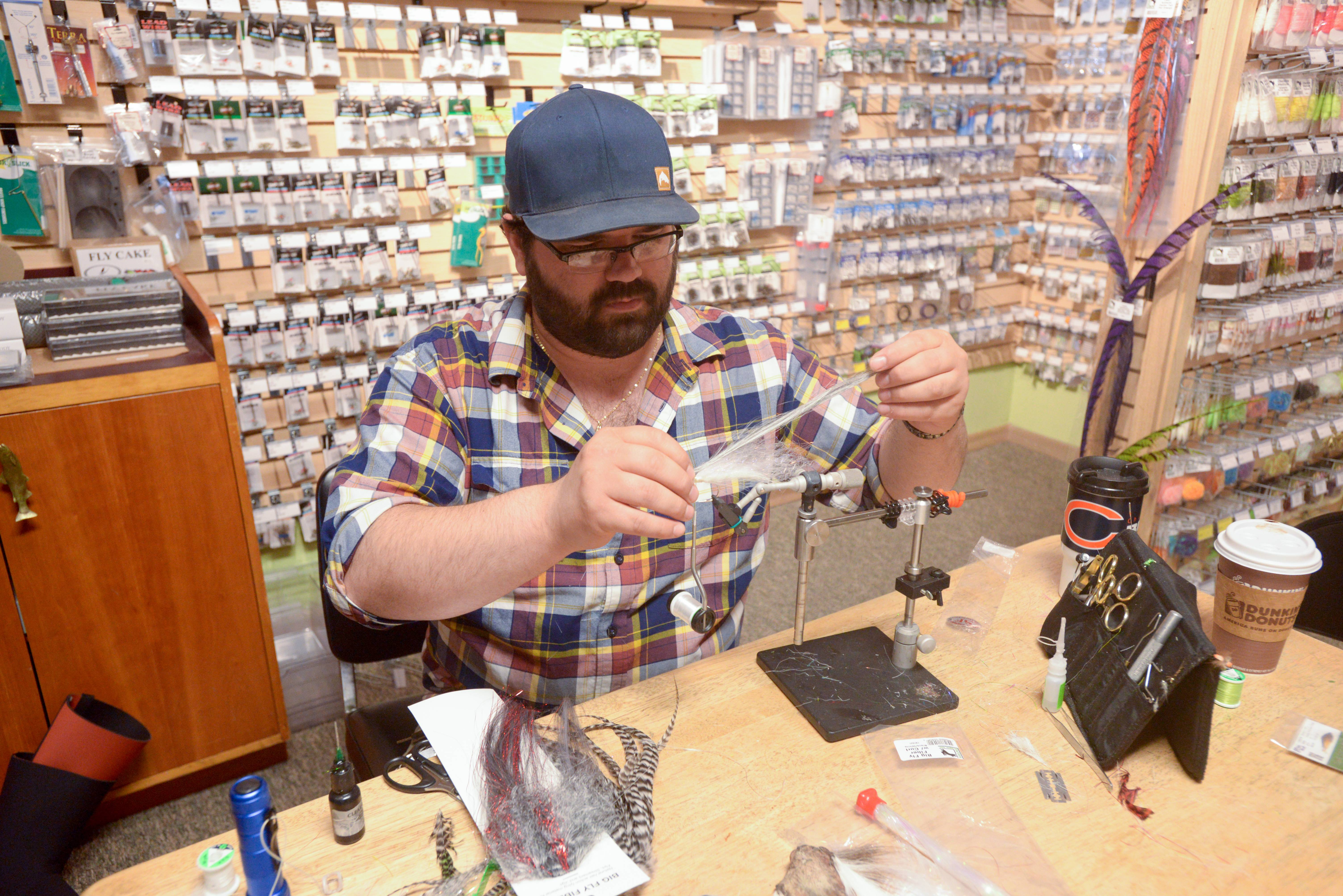 Jeremy Spaccapaniccia works on tying one of his musky flies in his Naperville fly shop, DuPage Fly Fishing Co.