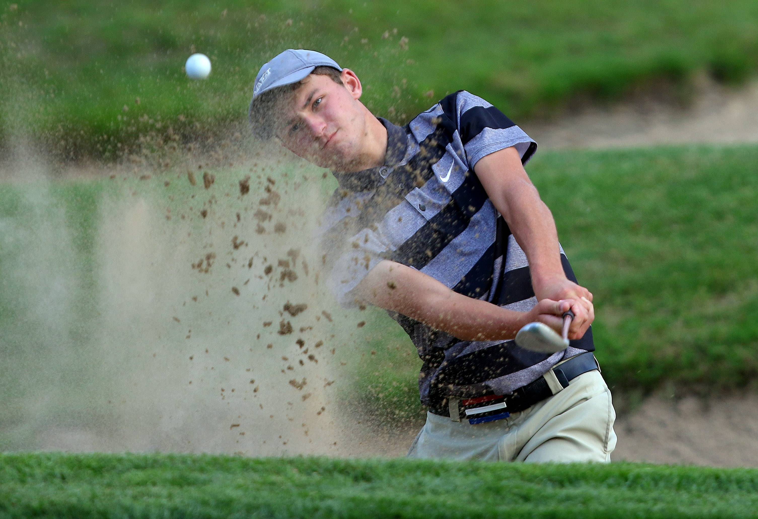 Libertyville's Jake Mueller hits from the bunker on the par-5 fourth hole on his way to a two under 34 against Mundelein Tuesday at Steeple Chase Golf Course in Mundelein.