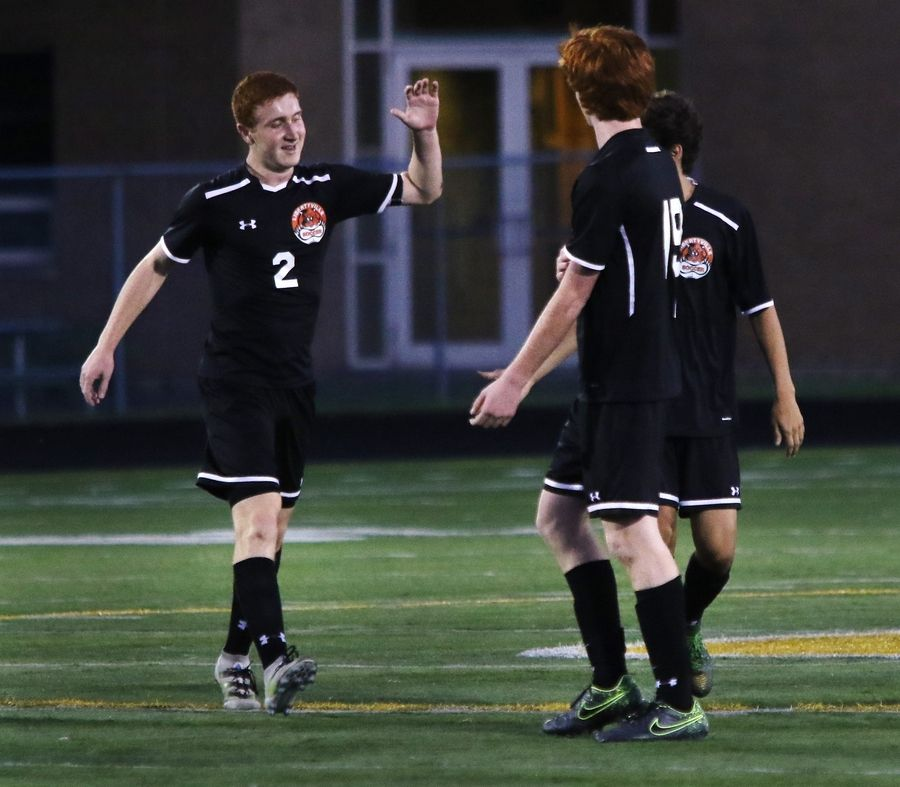 Libertyville forward Ryan Wittenbrink, left, congratulates Evan Rasmussen on his goal along with Kenny Gallagher in the first half Tuesday against host Stevenson.