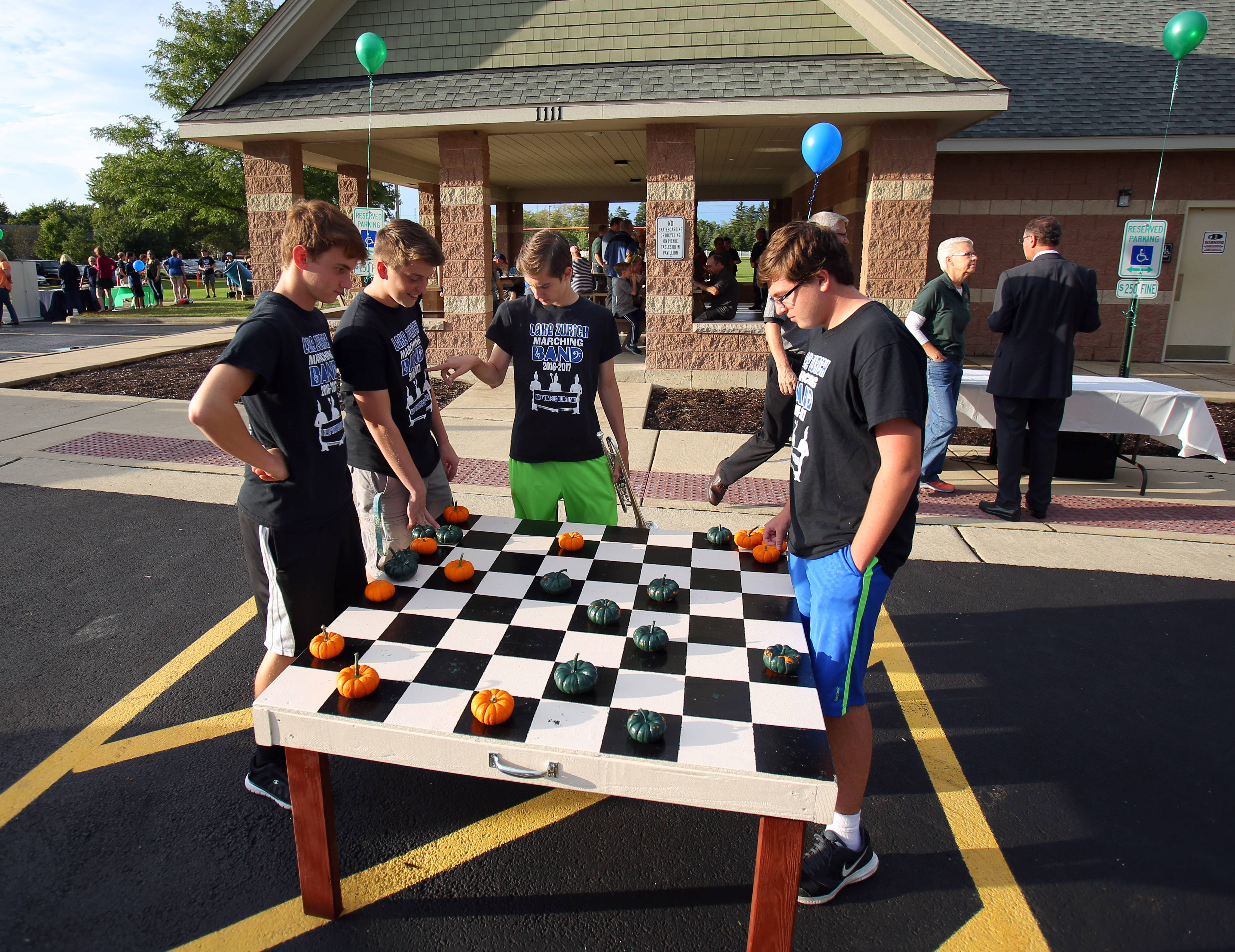 Members of the Lake Zurich High School marching band, from left, Steven Mueller, Nolan Foreman, Ethan Hepler and Eric Slaughter play checkers with pumpkins during the first Ela Day Wednesday at Knox Park in Lake Zurich.