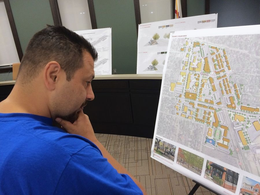 Mundelein resident Cesar Bolanos scrutinizes one of the development plans proposed for the town's downtown area during an open house at village hall.