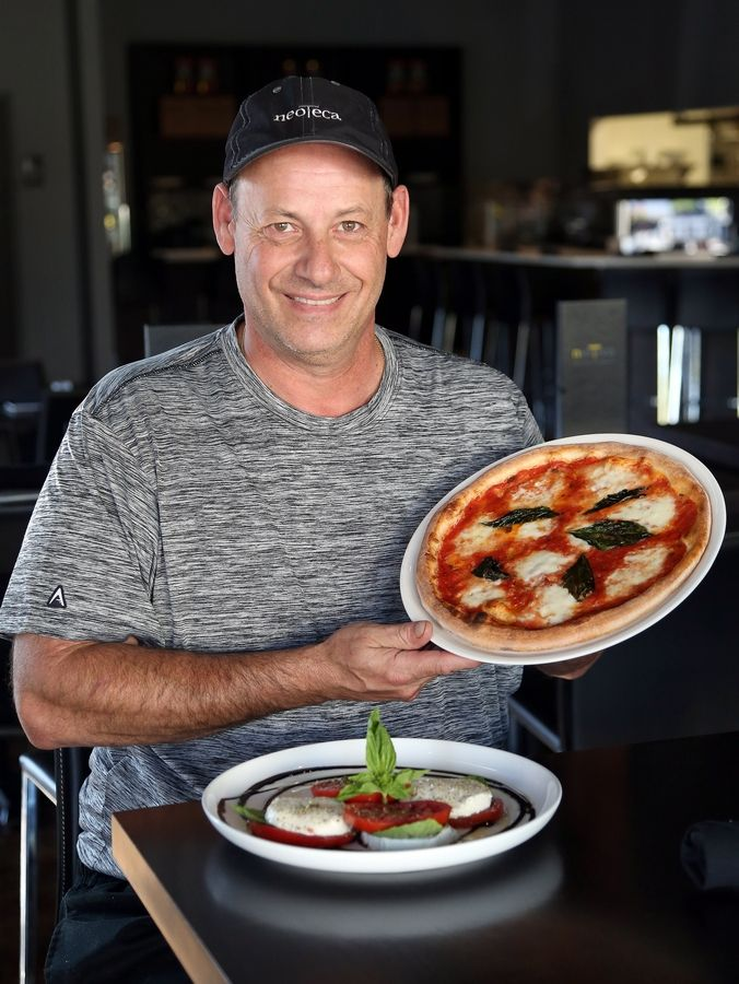 Neoteca Pizza & Wine Bar owner and chef Gaetano Sorrentino shows off a homemade brick-oven pizza and Caprese salad at the Barrington restaurant.