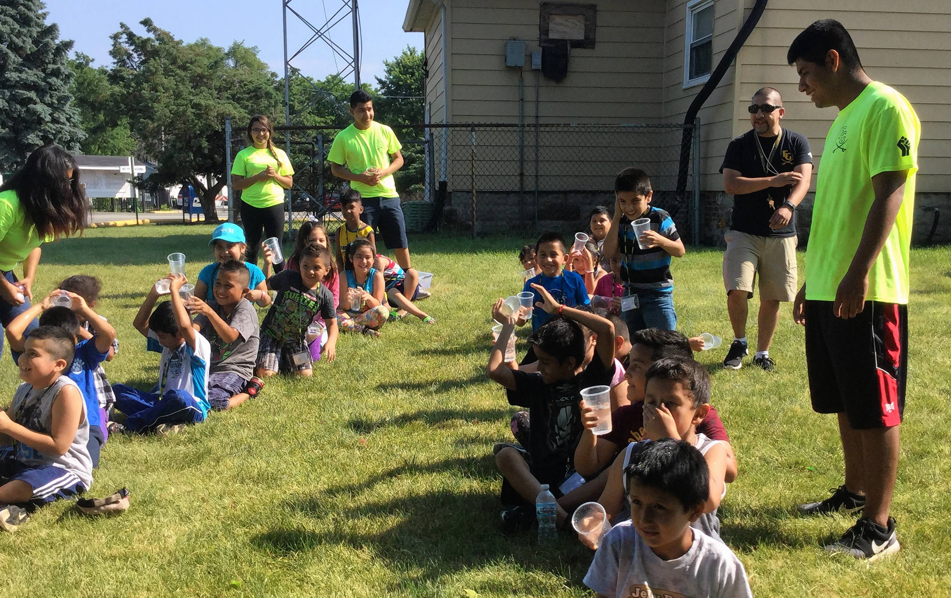 Students from Elk Grove High School created and volunteered as staff at a weeklong summer camp for children living in a mobile home community who do not live in a park district. Harper Promise scholar Maria Anzueto, left in the bright green shirt, helps leads children in an activity. Elk Grove student volunteers Dayanara Grimaldo, Roger Aguilera and Arturo Leaurano also lead the children's activity.