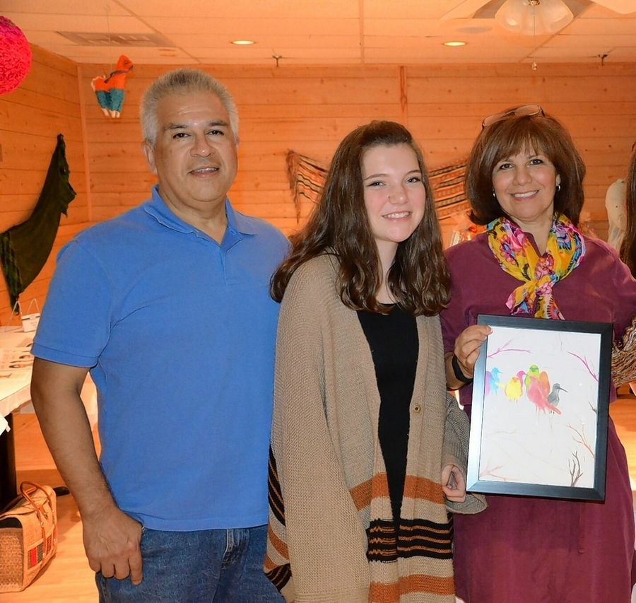 Harper Promise scholar Grace Gayhart stands with George and Yoli Alvin, founders of the Alyssa Alvin Foundation named after their daughter who died in July 2014 from leukemia. Grace holds a piece of her artwork, which was sold as part of a silent auction benefit for the foundation.