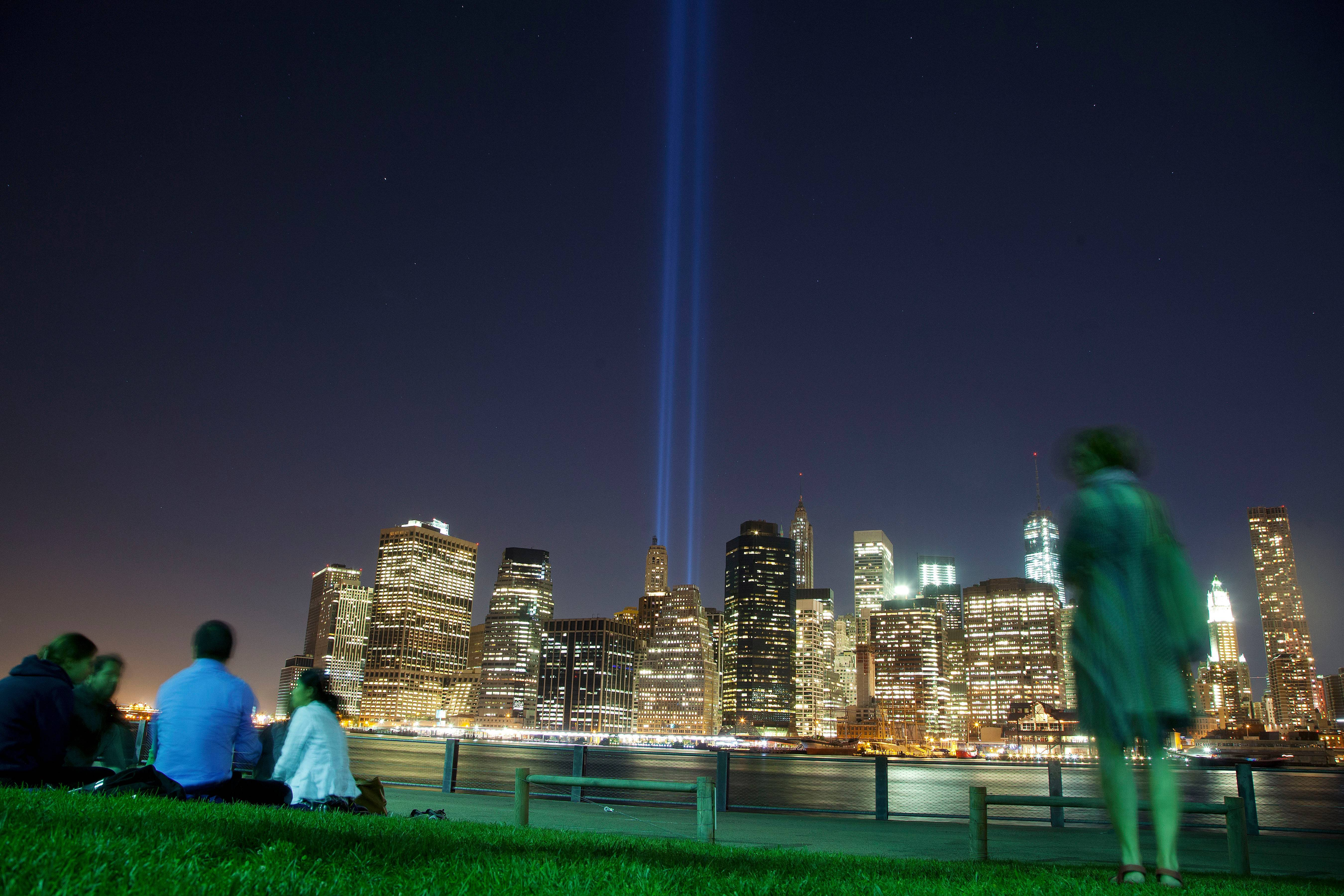 People in Brooklyn Bridge Park gather to watch the Tribute in Light rising from the lower Manhattan skyline in New York. The Tribute is on display Sept. 11 every year to mark the anniversary of the terrorist attacks.