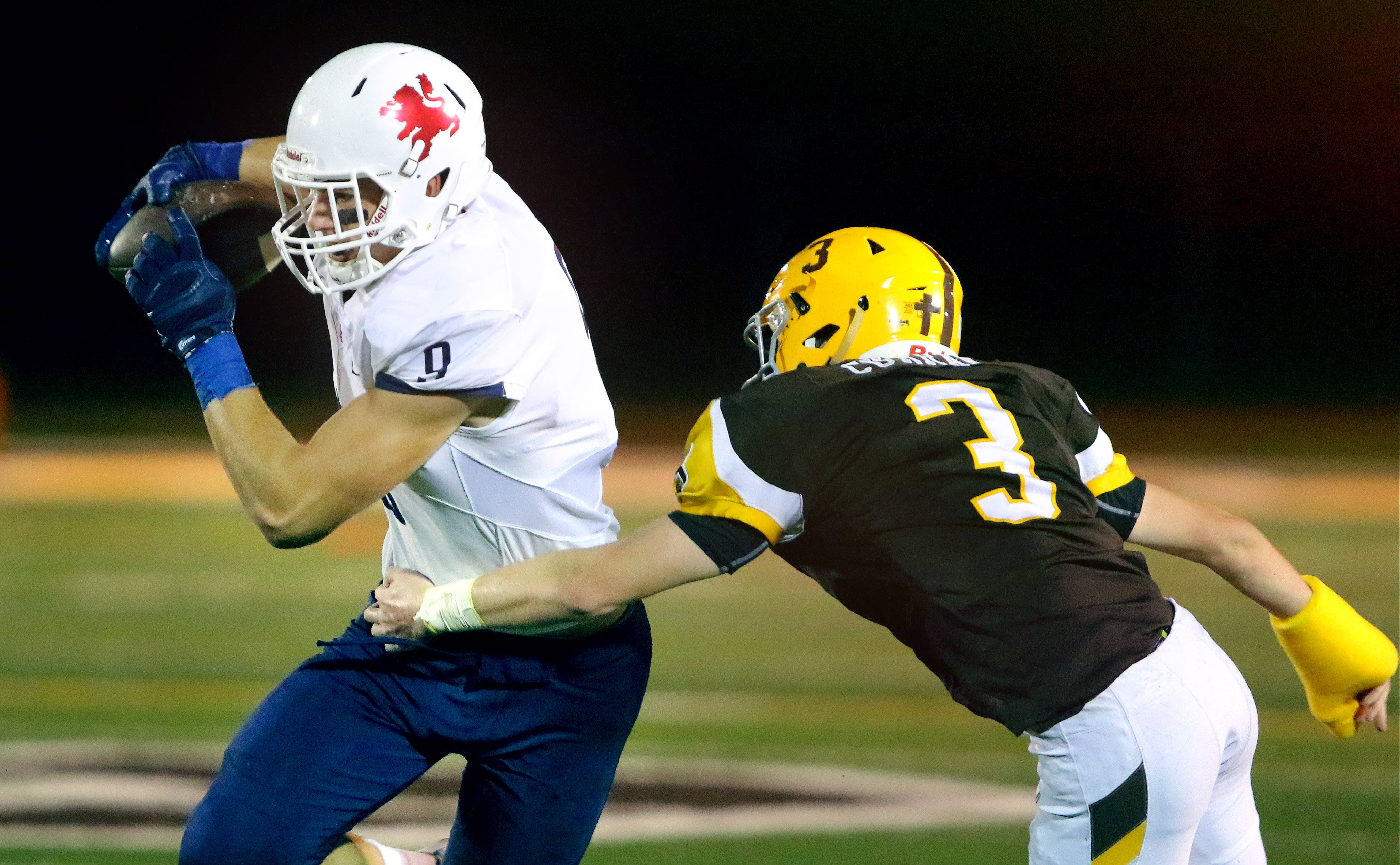 St. Viator's Cole Kmet, left, is pursued by Carmel Catholic's George Curran on Friday in Mundelein.