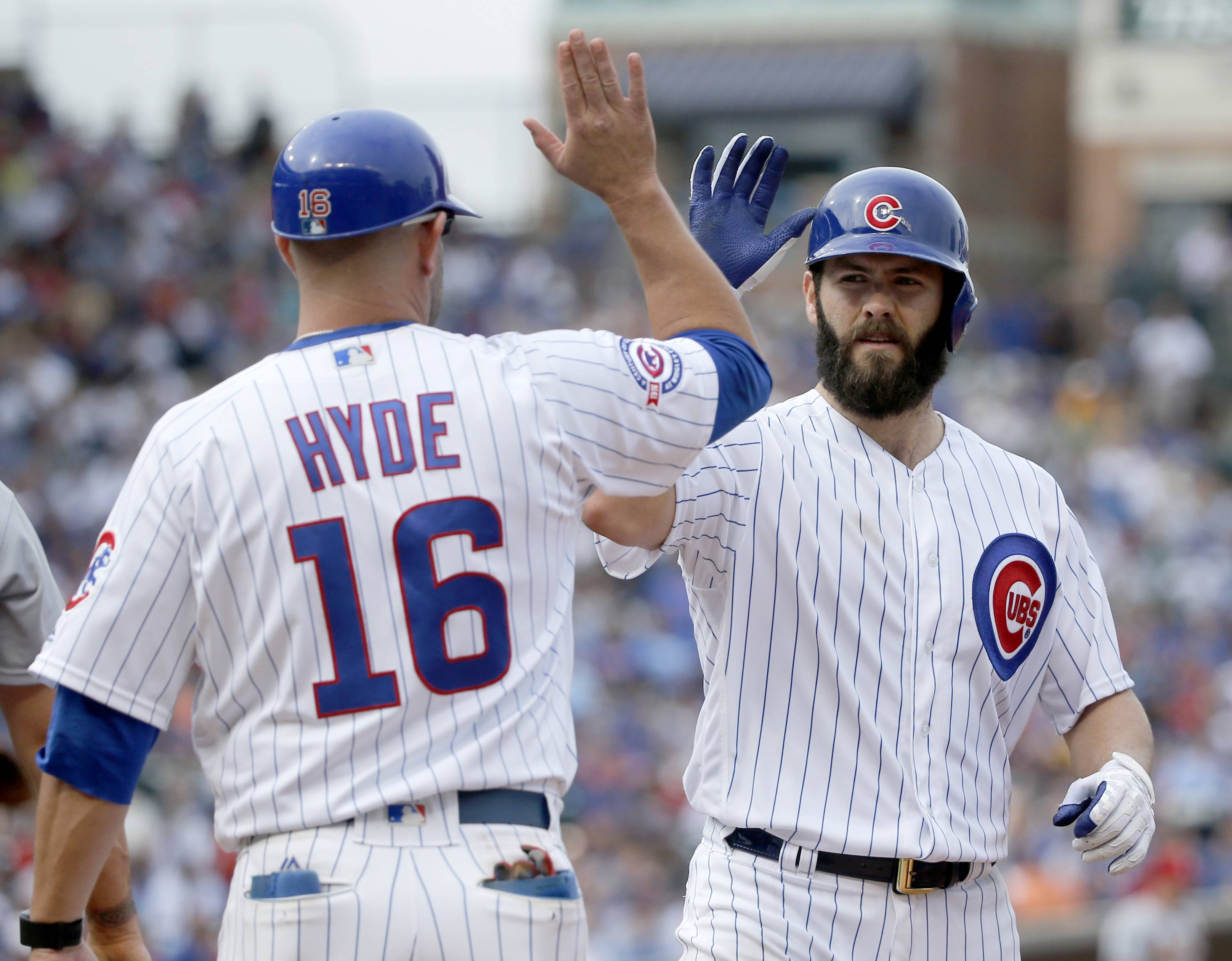 Cubs first base coach Brandon Hyde greets Jake Arrieta at first after Arrieta's single off St. Louis Cardinals starting pitcher Mike Leake during the fourth inning on Friday in Chicago.