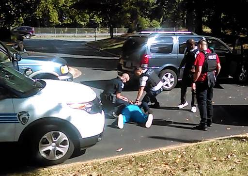 In this image taken from video recorded by Keith Lamont Scott's wife, Rakeyia Scott, on Tuesday, Sept. 20, 2016, Charlotte police squat next to Keith Lamont Scott as Scott lies face-down on the ground, in Charlotte, N.C. In the video of the deadly encounter between Charlotte police and the black man, Rakeyia Scott repeatedly tells officers her husband is not armed and pleads with them not to shoot him as they shout at him to drop a gun. The video does not show clearly whether Scott had a gun. (Rakeyia Scott/Curry Law Firm via AP)