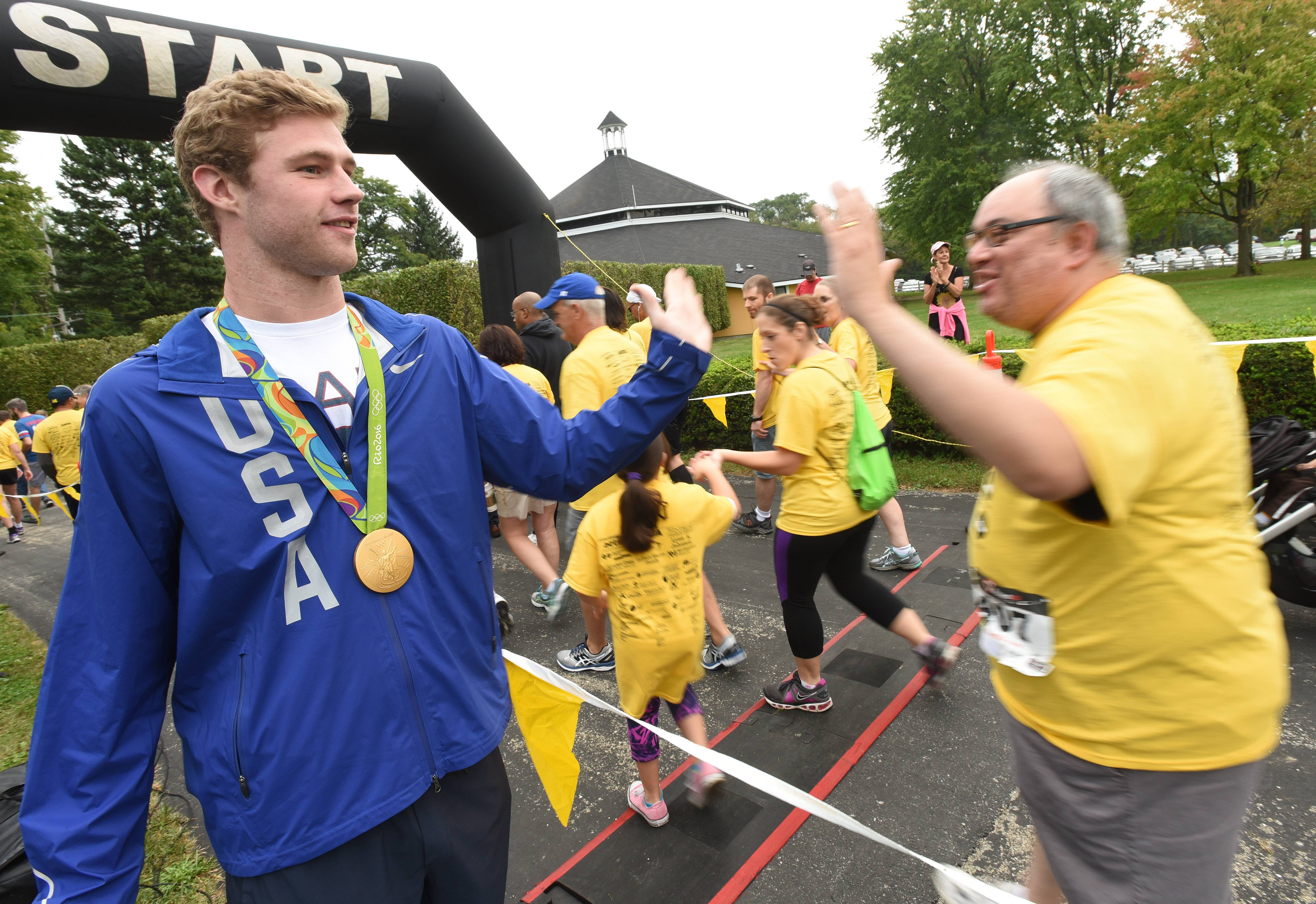 Olympic swimmer Kevin Cordes of Naperville high-fives runners as they start their run during Saturday's Run for the Mind at St. James Farm near Warrenville.