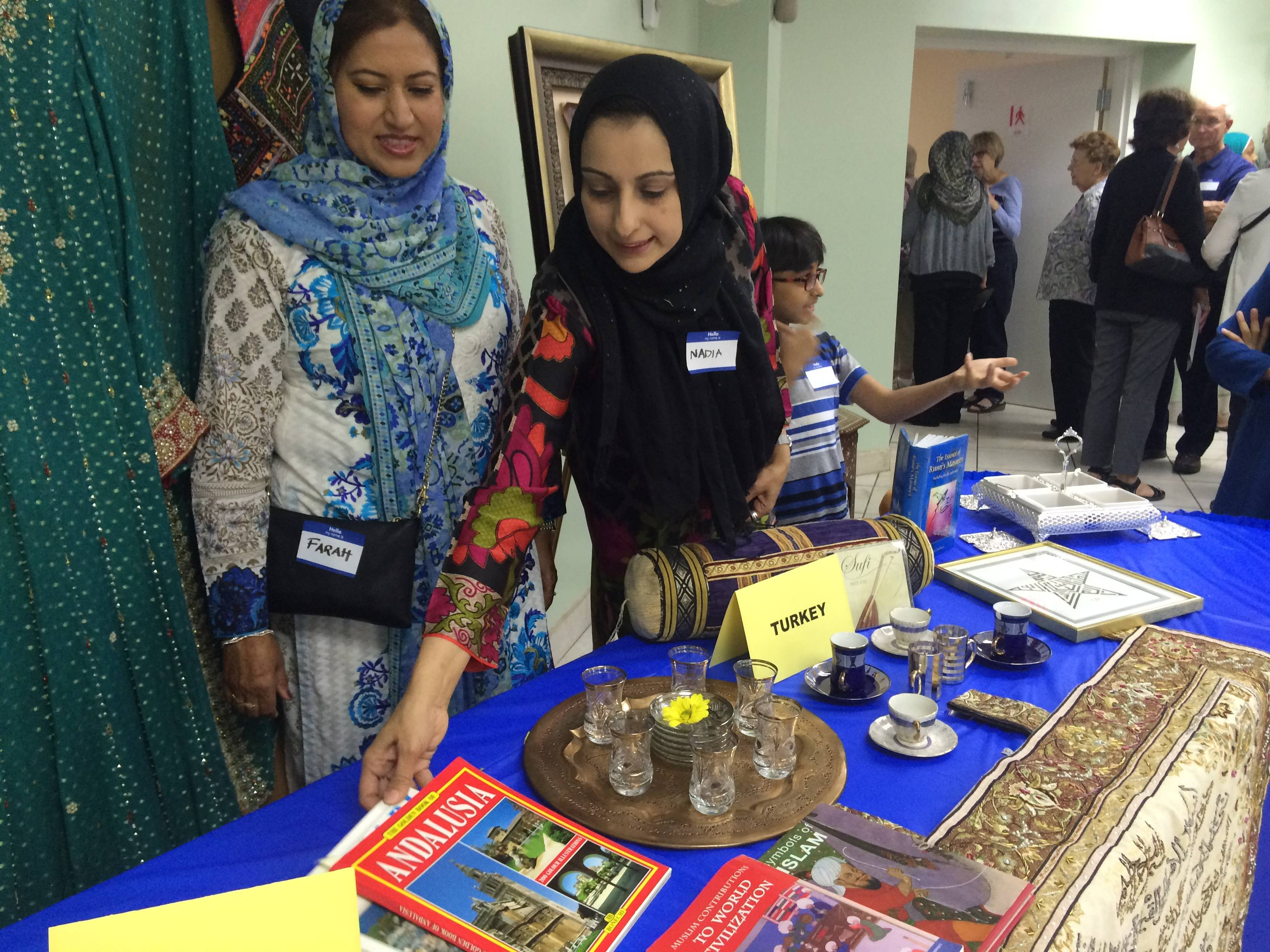 Farah Ahmed of Vernon Hills, left, and Nadia Shah of Long Grove show objects from Turkey and other Islamic countries during an open house Saturday at Islamic Foundation North in Libertyville.