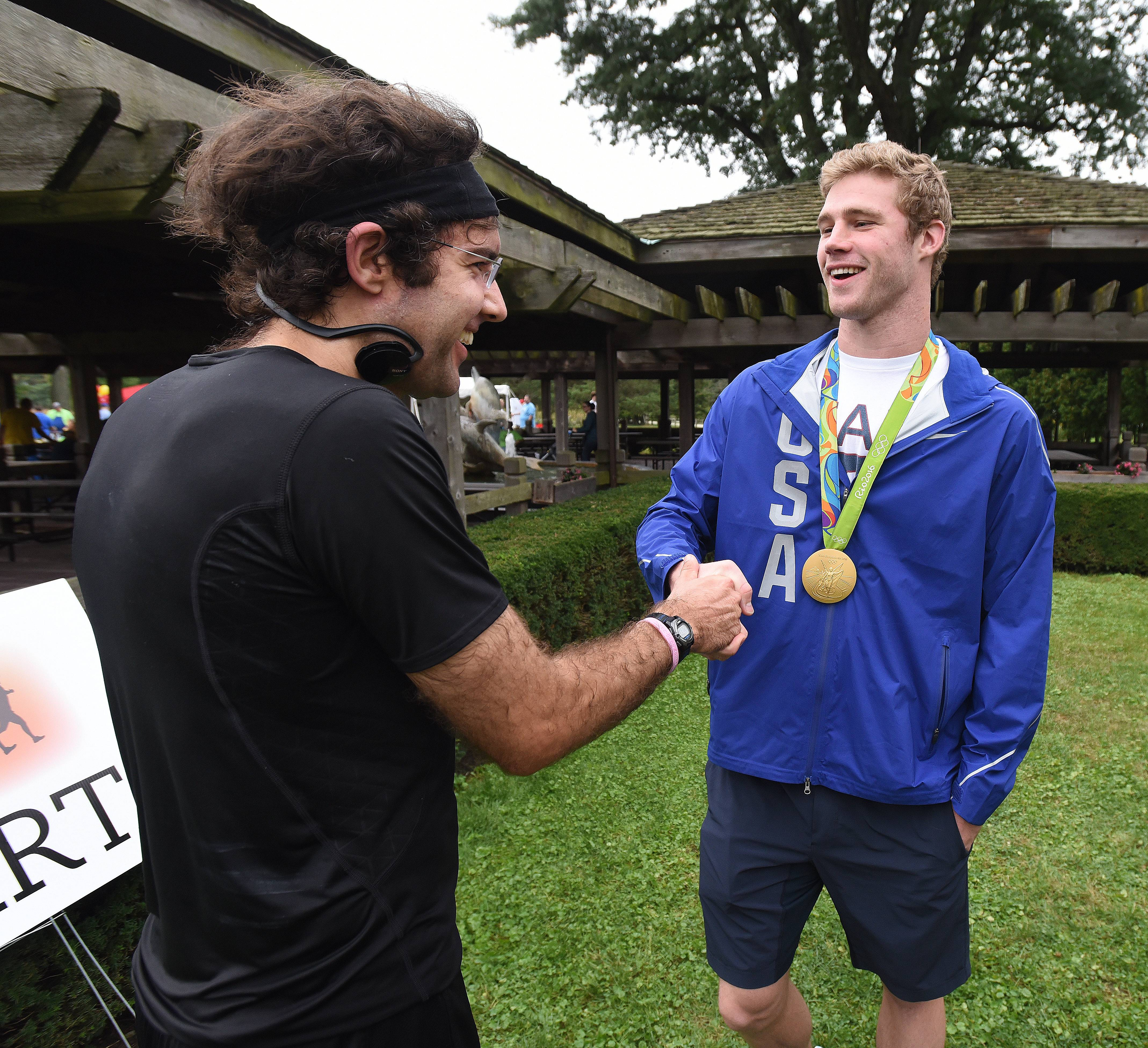 After winning his race, Wes Schoenfeldt of Naperville was congratulated by Olympic swimmer Kevin Cordes during Saturday's Run for the Mind at St. James Farm near Warrenville.