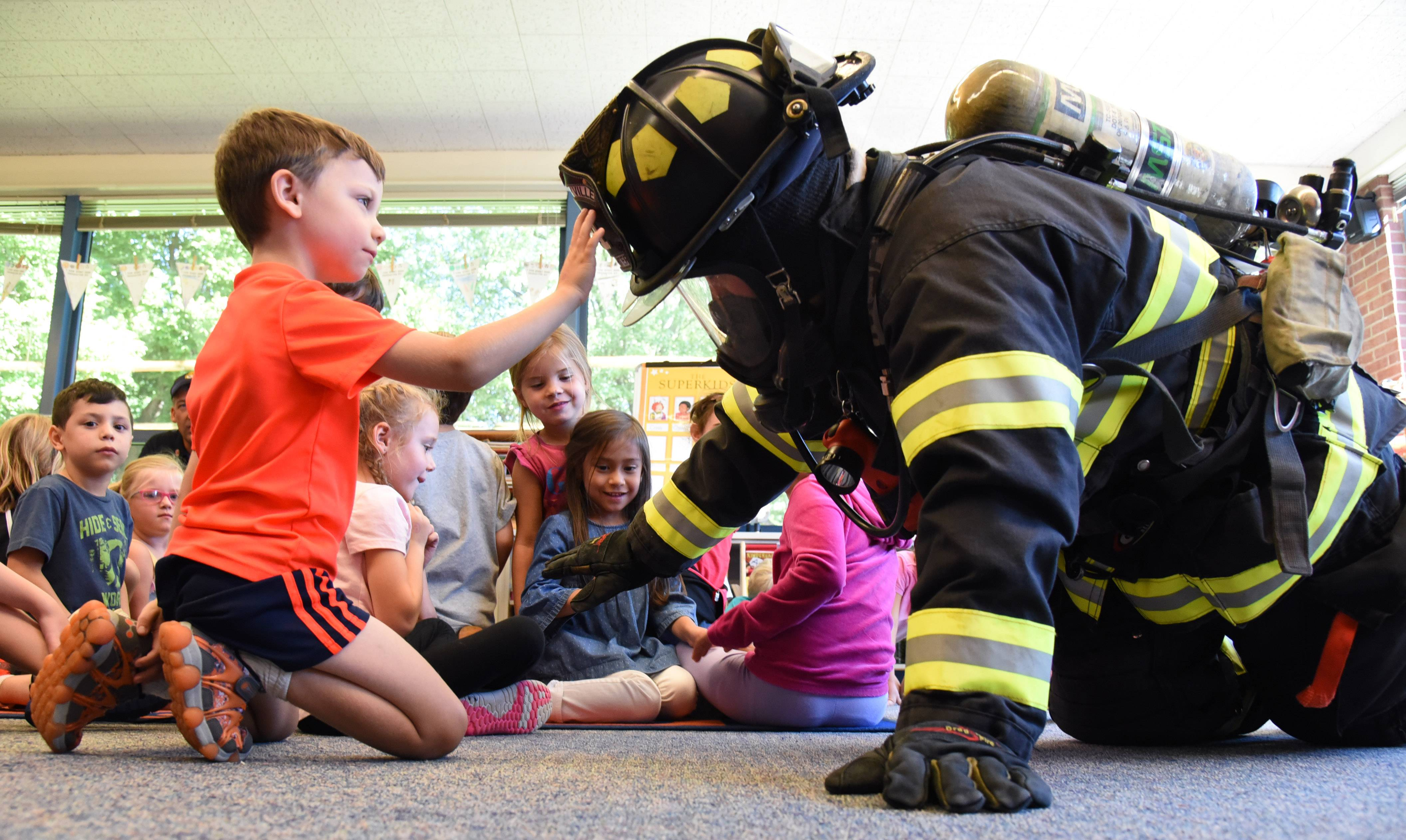 Copeland Manor School kindergarten student Max Buttita checks out the helmet of Libertyville firefighter Jered Woodward during a visit Tuesday to the school.