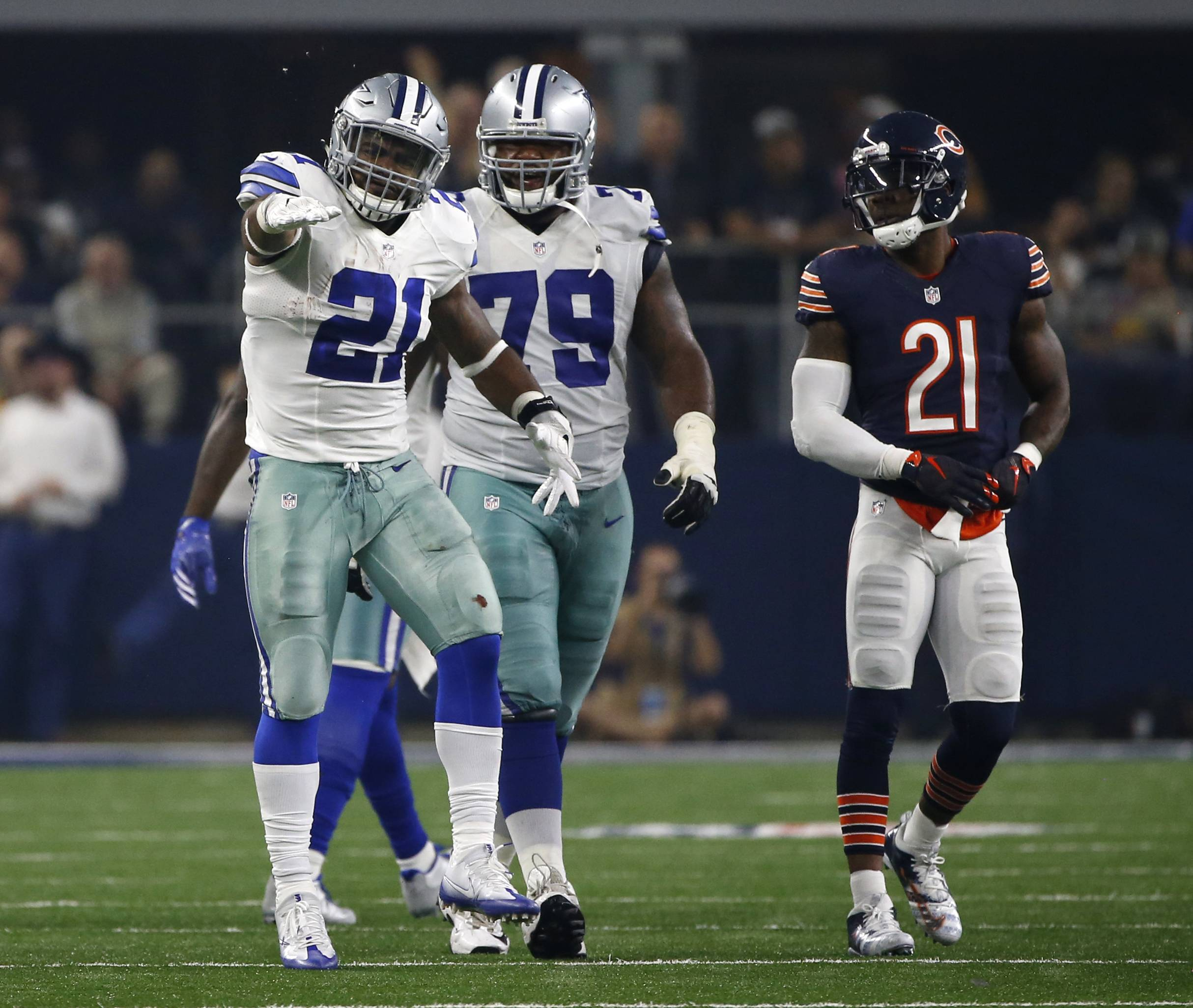 Dallas Cowboys running back Ezekiel Elliott (21) and Chaz Green (79) celebrate a run for first down by Elliott as Chicago Bears cornerback Tracy Porter (21) watches in the second half of an NFL football game, Sunday, Sept. 25, 2016, in Arlington, Texas. (AP Photo/Ron Jenkins)
