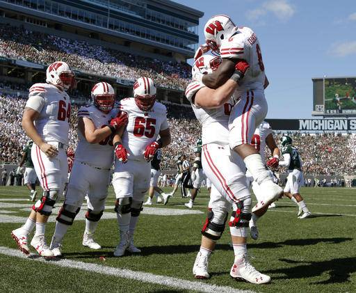 Wisconsin's Corey Clement, right, celebrates his touchdown against Michigan State with teammates, from left, Brett Connors, Michael Deiter, Olive Sagapolu (65) and Beau Benzschawel during the third quarter of an NCAA college football game, Saturday, Sept. 24, 2016, in East Lansing, Mich. Wisconsin won 30-6. (AP Photo/Al Goldis)