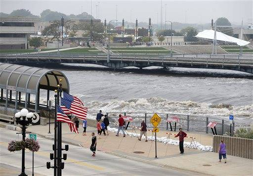 People view the flooding on the Cedar River in downtown Waterloo, Iowa, Saturday, Sept. 24, 2016. (Brandon Pollock/The Courier via AP)