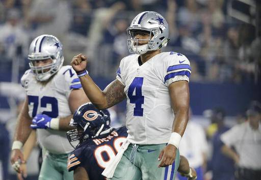 Dallas Cowboys quarterback Dak Prescott (4) celebrates a touchdown catch by wide receiver Dez Bryant in the second half of an NFL football game against the Chicago Bears on Sunday, Sept. 25, 2016, in Arlington, Texas. (AP Photo/LM Otero)