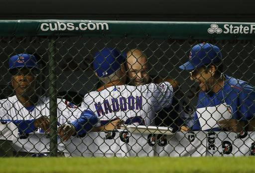 Chicago Cubs catcher David Ross hugs manager Joe Maddon in the dugout after Willson Contreras replaced David Ross during the seventh inning of a baseball game against the St. Louis Cardinals Sunday, Sept. 25, 2016, in Chicago. (AP Photo/Nam Y. Huh)