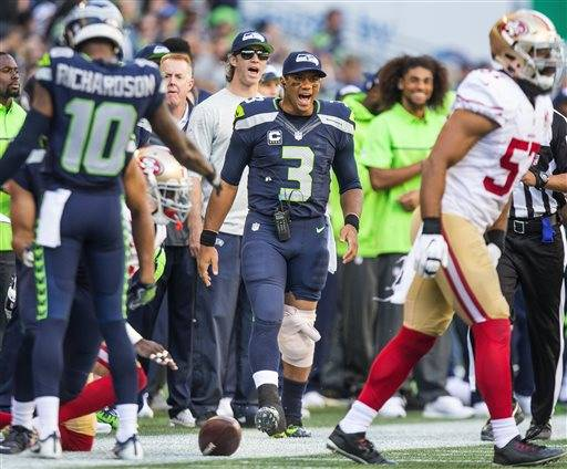 Seattle Seahawks quarterback Russell Wilson cheers his team as he stands on the sidelines with his leg wrapped in ice during an NFL football game against the San Francisco 49ers, Sunday, Sept. 25, 2016, in Seattle. (Dean Rutz/The Seattle Times via AP)