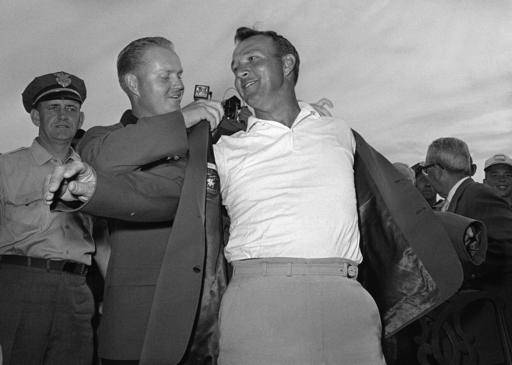 "FILE - In this April 12, 1964 file photo, Arnold Palmer, right, slips into his green jacket with help from Jack Nicklaus after winning the Masters golf championship, in Augusta, Ga. Palmer, who made golf popular for the masses with his hard-charging style, incomparable charisma and a personal touch that made him known throughout the golf world as ""The King,"" died Sunday, Sept. 25, 2016, in Pittsburgh. He was 87. (AP Photo/File)"