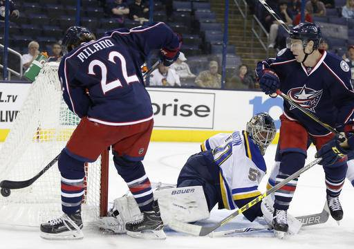 St. Louis Blues' Jordan Binnington, center, makes a save against Columbus Blue Jackets' Sonny Milano, left, and Matt Calvert during the second period of a preseason NHL hockey game Sunday, Sept. 25, 2016, in Columbus, Ohio. (AP Photo/Jay LaPrete)