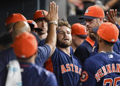 Houston Astros' Tyler White, center, celebrates his solo home run off Los Angeles Angels relief pitcher Brett Oberholtzer with teammates in the seventh inning of a baseball game, Sunday, Sept. 25, 2016, in Houston. (AP Photo/Eric Christian Smith)