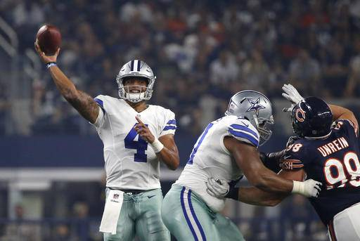 Dallas Cowboys quarterback Dak Prescott (4) throws a pass under pressure from Chicago Bears defensive end Mitch Unrein in the first half of an NFL football game, Sunday, Sept. 25, 2016, in Arlington, Texas. (AP Photo/Ron Jenkins)