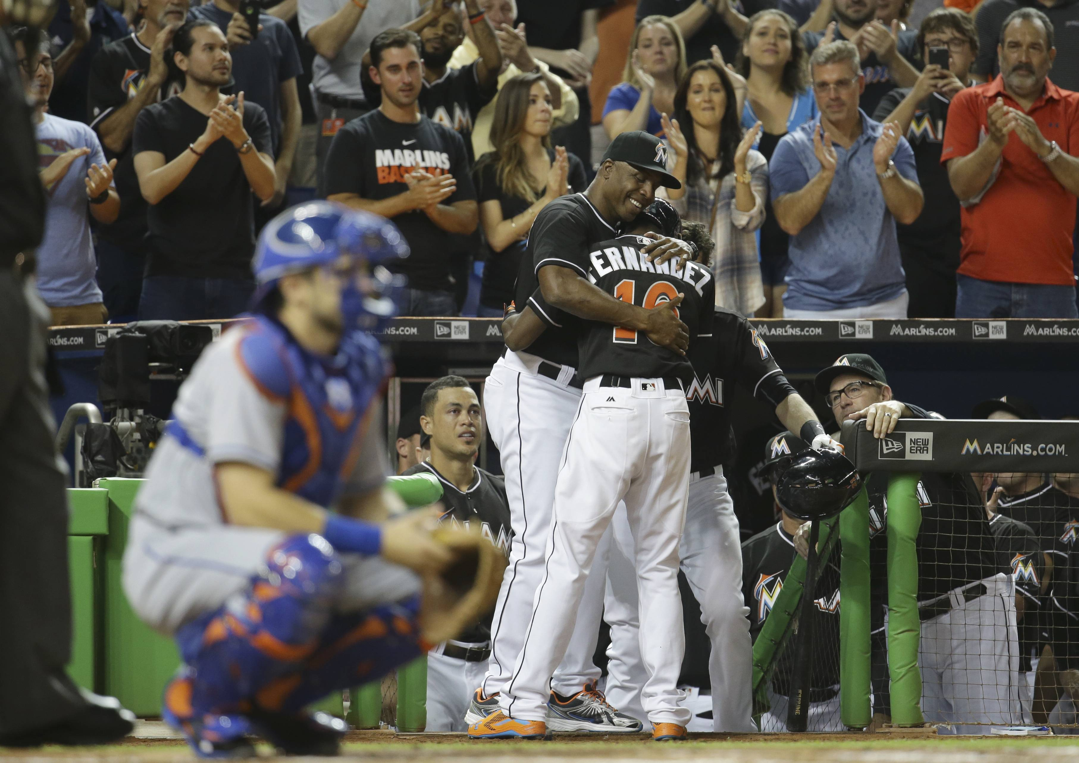 Miami Marlins hitting coach Barry Bonds, left, hugs Dee Gordon, right, after he hit a solo home run during the first inning in a baseball game against the New York Mets, Monday in Miami.