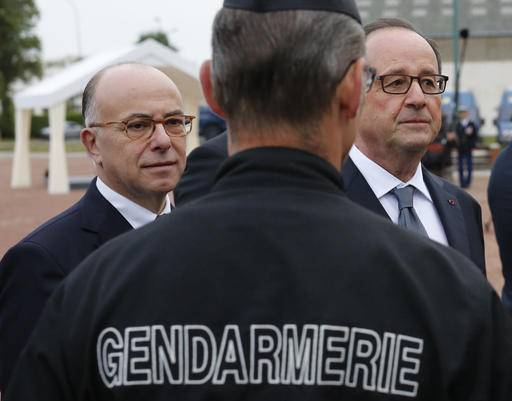 French President Francois Hollande, right, and French Interior Minister Bernard Cazeneuve meet with Gendarme officers during their visit in Calais, northern France, Monday Sept. 26 2016. Hollande says the migrant camp in Calais must be fully dismantled by the end of the year. (Thibault Vandermersch, Pool photo via AP)
