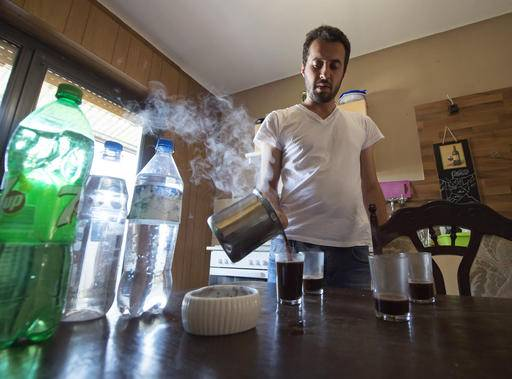 In this photo taken Monday, Aug. 15, 2016, Mohammed al-Haj makes coffee in his home in Saarbruecken, Germany. Al-Haj, a native of the city of Aleppo, Syria's one-time economic capital that now lies in ruins, came to the western German state of Saarland in September 2015 to benefit from its swift processing of migrants. (AP Photo/Jens Meyer)