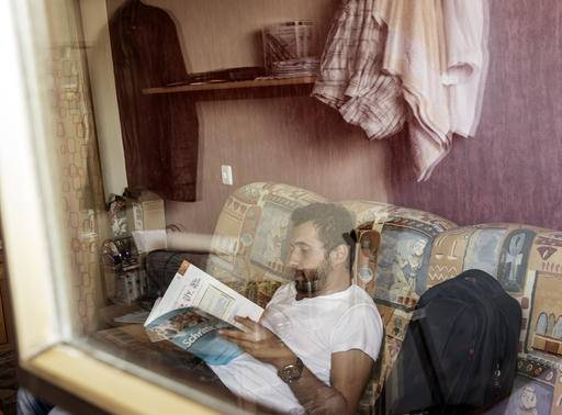 In this photo taken Tuesday, Aug. 16, 2016, through a window with reflections Mohammed al-Haj learns German in his home in Saarbruecken, Germany. Al-Haj, a native of the city of Aleppo, Syria's one-time economic capital that now lies in ruins, came to the western German state of Saarland in September 2015 to benefit from its swift processing of migrants. (AP Photo/Jens Meyer)