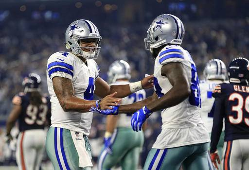 Dallas Cowboys' Dak Prescott (4) and Dez Bryant (88) celebrate a touchdown catch caught by Bryant in the second half of an NFL football game against the Chicago Bears on Sunday, Sept. 25, 2016, in Arlington, Texas. (AP Photo/Ron Jenkins)