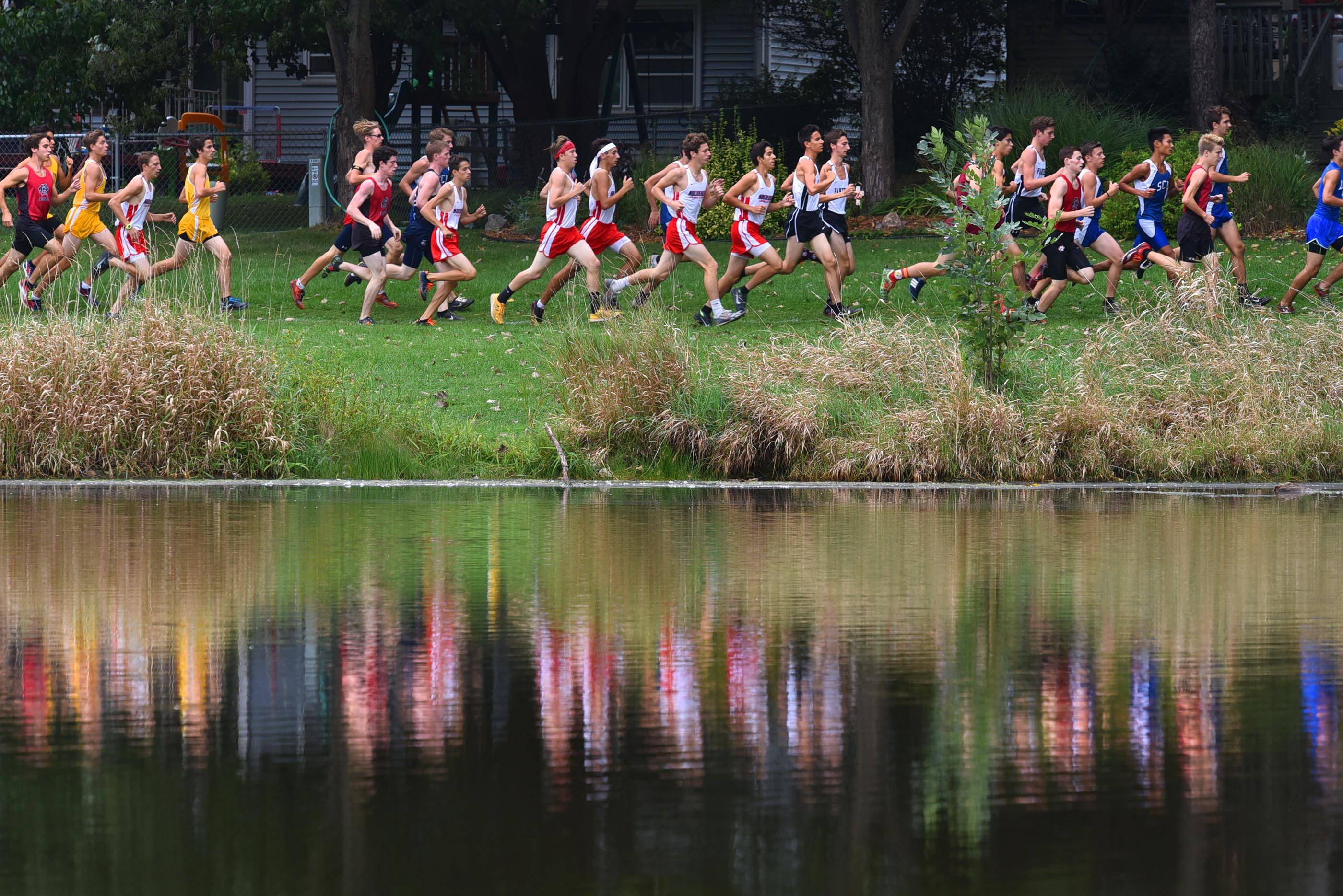 Runners compete along the edge of a pond at Sunrise Park in the boys varsity race Saturday at the Bartlett cross-country invitational.