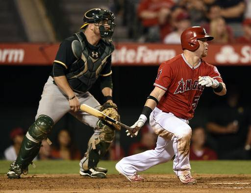 Los Angeles Angels' Kole Calhoun watches his RBI triple in front of Oakland Athletics catcher Stephen Vogt during the fourth inning of a baseball game in Anaheim, Calif., Tuesday, Sept. 27, 2016. (AP Photo/Kelvin Kuo)