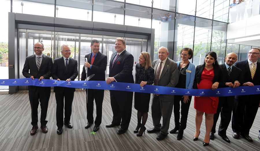 Zurich North America CEO Mike Foley prepares to cut the ribbon on the company's new headquarters Wednesday in Schaumburg as Chief Legal Officer Dennis Kerrigan and Business Lead Jennifer Kyung look on.