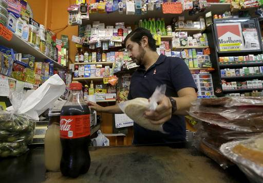 Alex Del Rio works behind the counter at his family's market El Ahorro in San Francisco, Wednesday, Sept. 21, 2016. In November 2016, voters in San Francisco and Oakland will consider a penny per ounce tax on sugar laden drinks such as bottled cola, sports drinks and iced teas in November. (AP Photo/Jeff Chiu)