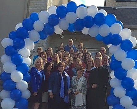 Faculty, staff and Pastor Bernie Pietrzak of St. Anne Parish School in Barrington pose beneath an arch of blue and white balloons to celebrate their Blue Ribbon award Wednesday.