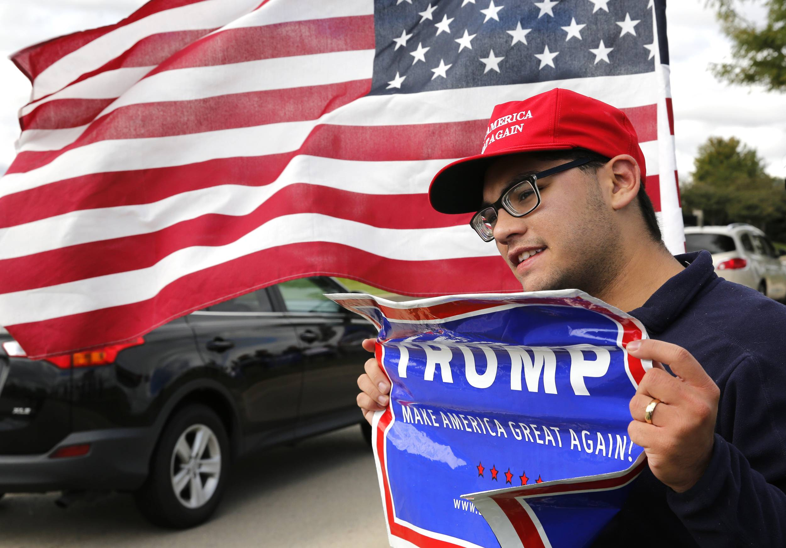 Alexander Rodriguez of Joliet shows his Donald Trump support Wednesday outside the Bolingbrook Golf Club during a fundraiser for the Republican candidate.