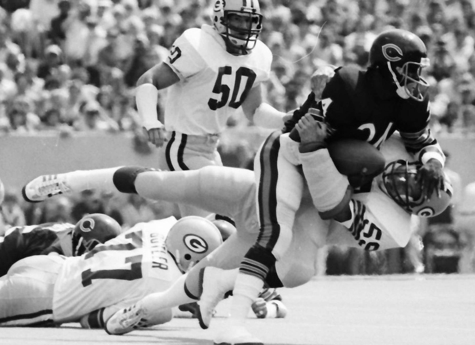 John Anderson of the Packers tackles Walter Payton of the Bears during a game between the Green Bay Packers and the Chicago Bears at Soldier Field in Chicago on Sept. 6, 1981.