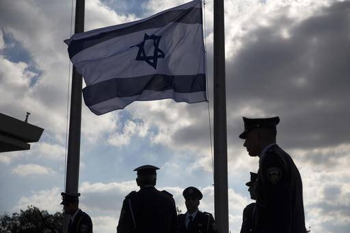 Members of the Knesset guard stand next to the Israeli flag at half-staff in preparations to display the coffin of former Israeli President Shimon Peres at the Knesset, Israel's Parliament, in Jerusalem, Wednesday, Sept. 28, 2016. The country mourned the death of Peres, a former president and prime minister whose life story mirrored that of the Jewish state, as the government began preparations for a funeral that is expected to bring together world leaders and dignitaries. Israeli officials are feverishly preparing security arrangements and logistics to host an array of world figures arriving in Israel for Peres' funeral Friday. (AP Photo/Ariel Schalit)