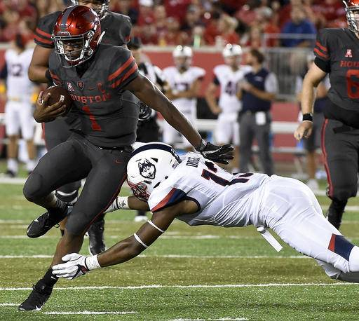 Houston quarterback Greg Ward Jr. (1) breaks the tackle of Connecticut linebacker Vontae Diggs en route to a 30-yard touchdown in the first half of an NCAA college football game, Thursday, Sept. 29, 2016, in Houston. (AP Photo/Eric Christian Smith)