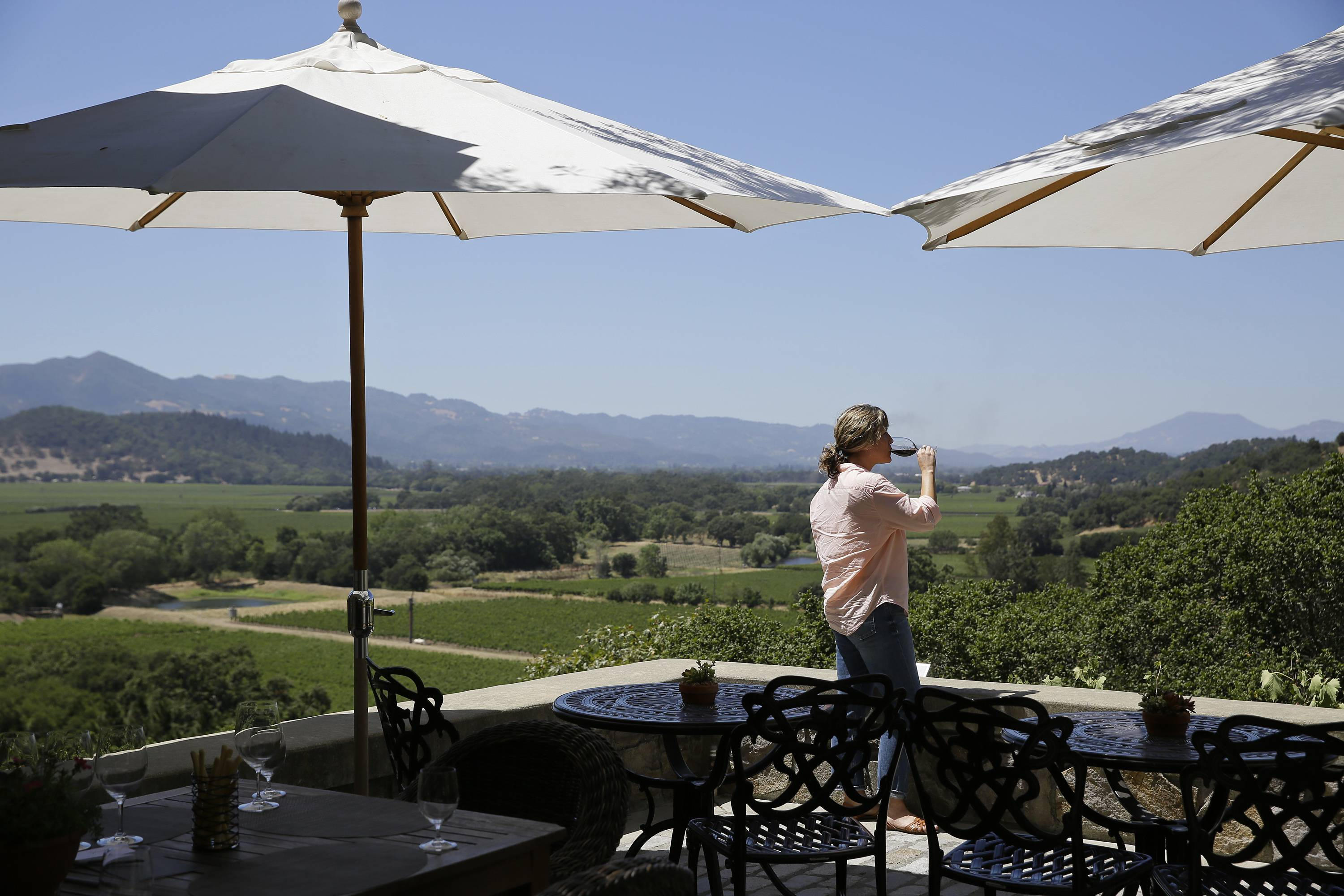 A woman drinks a glass of wine and takes in the view from the tasting room terrace at Silverado Vineyards in Napa, Calif.