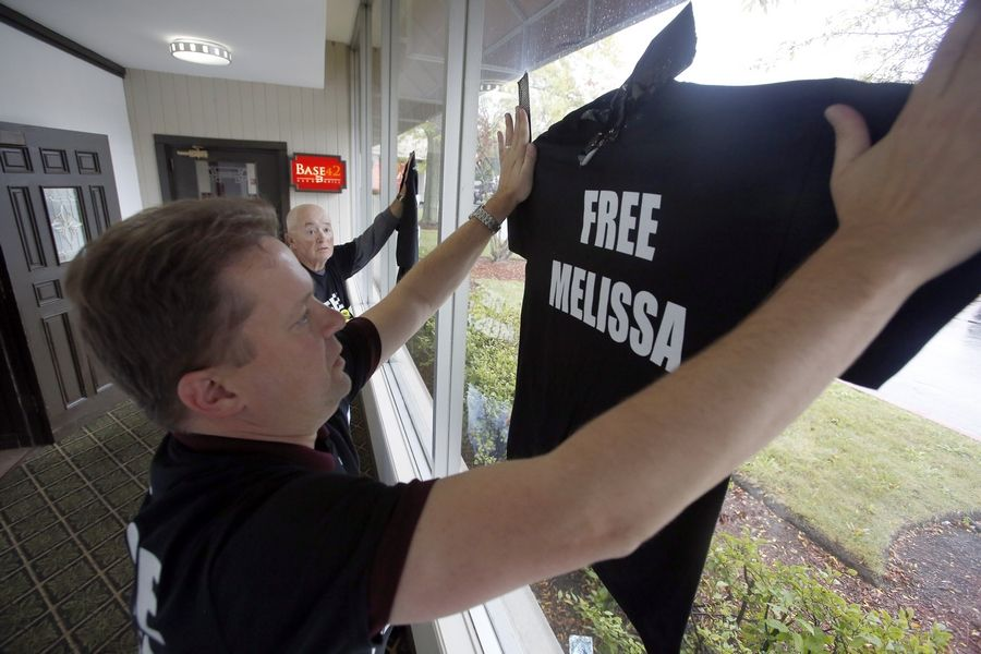 "Scott Panek, of Waukegan closest to camera, and Russell Jackson of Elgin hang ""Free Melissa"" shirts Friday before a news conference in Waukegan. A Lake County judge refused to grant a new trial for Melissa Calusinski, who was convicted in 2011 of killing a toddler at a day care center where she worked."