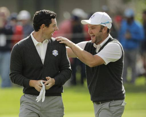 Europe's Andy Sullivan congratulates Europe's Rory McIlroy after McIlroy holed his approach shot on the sixth hole during a practice round for the Ryder Cup golf tournament Thursday, Sept. 29, 2016, at Hazeltine National Golf Club in Chaska, Minn. (AP Photo/Charlie Riedel)