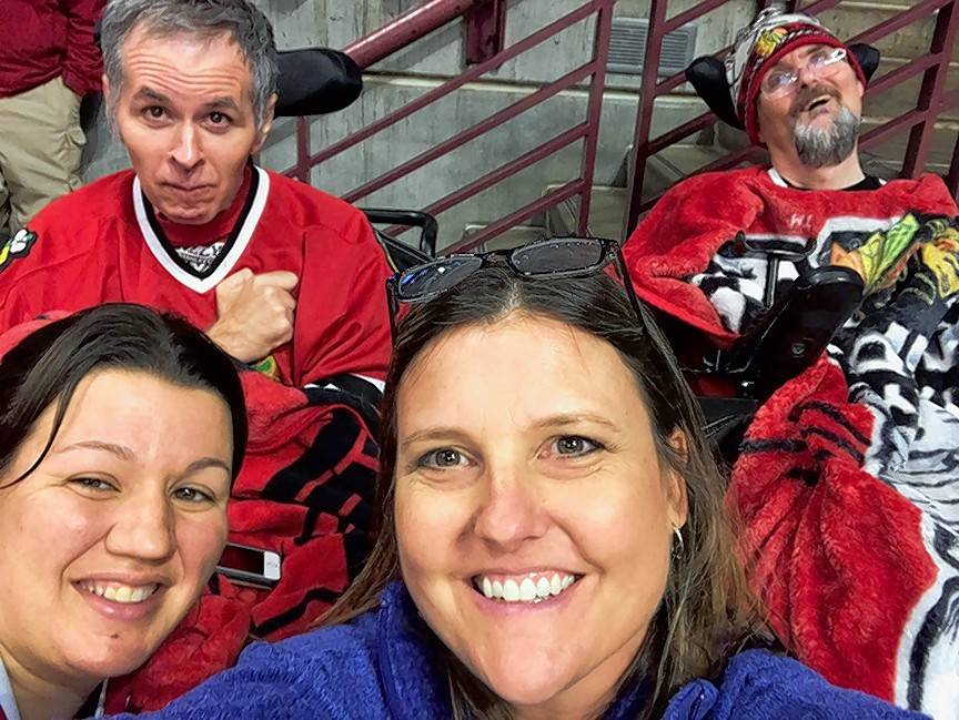 Brothers Brad, left, and Phil, clients at Marklund in Geneva, pose for a selfie with Marklund registered nurse Tori Jenkins, center, and certified nursing assistant Stephanie Dellegrazie during a Chicago Blackhawks game.