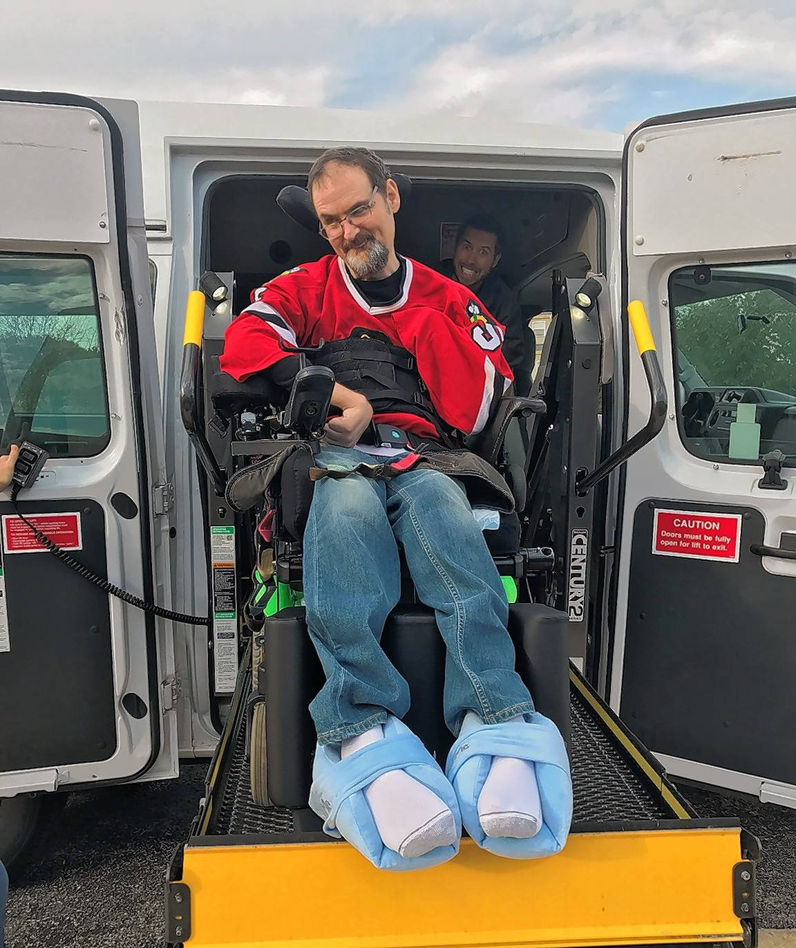 Marklund client Phil gets ready for a ride to the Blackhawks game, with assistance from Marklund's maintenance technician Paul Rogers.