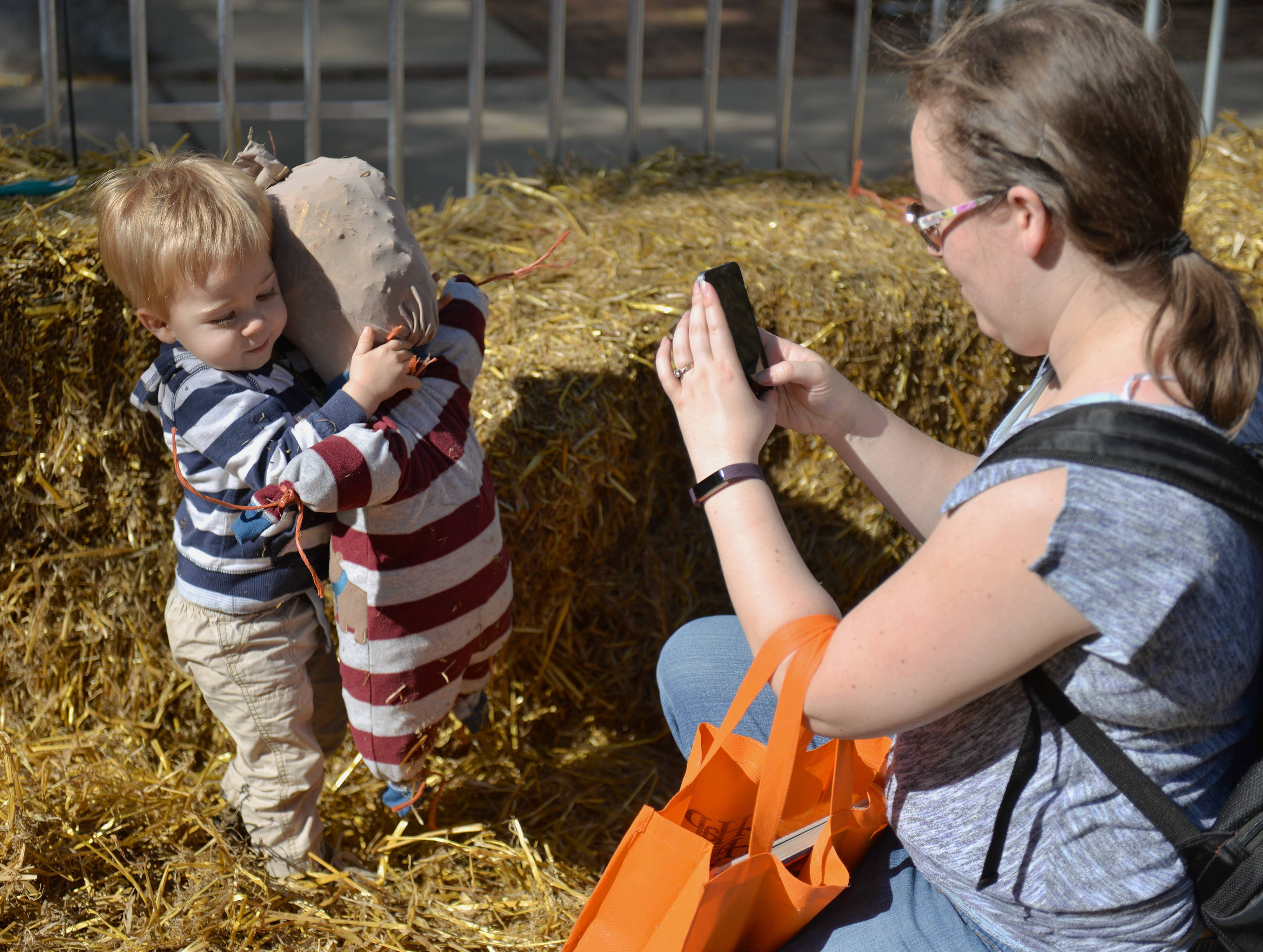 Kelly Gandy of Warrenville photographs her son Benjamin as he tries to hold up a scarecrow they made together Saturday at St. Charles Scarecrow Fest.